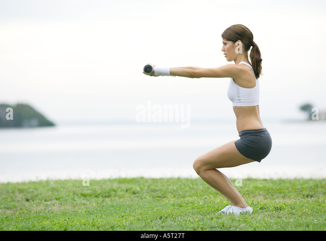 Young woman working out with weights, outdoors - Stock Image