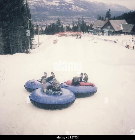 Three children begin their slide down a hill on innertubes. - Stock Image