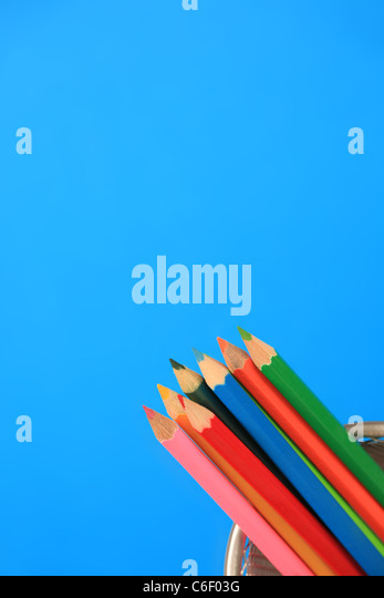 Multi coloured pencils in a pot, blue background. - Stock Image