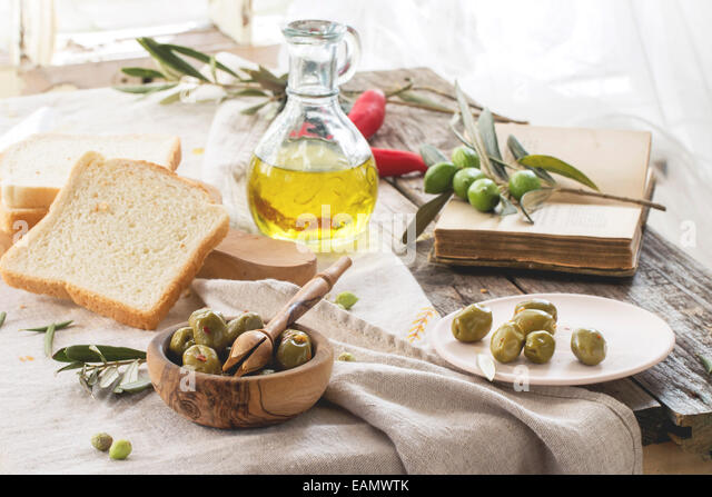 Lunch with green olives, bread and olive oil served with vintage book on old wooden table near window. - Stock Image