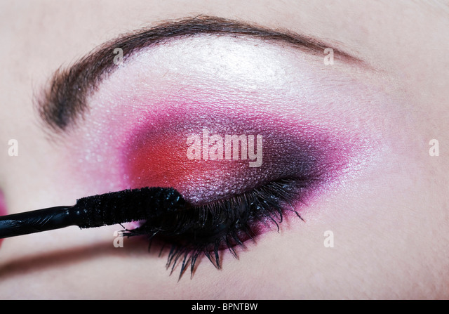 woman applying mascara colored eyeshadow makeup - Stock Image