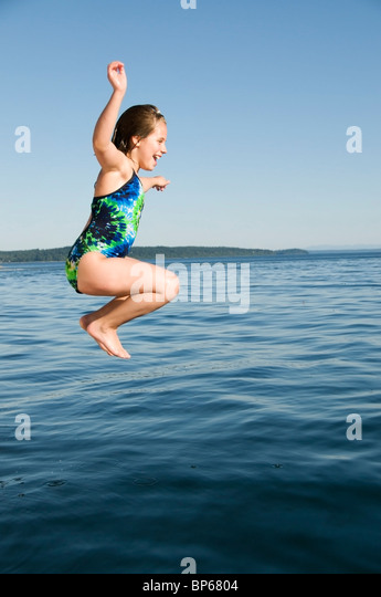 A happy girl jumps from a boat into the chilly saltwater near McMicken Island in south Puget Sound. - Stock-Bilder