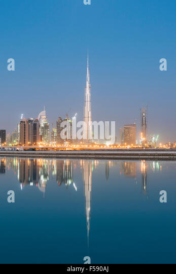 Skyline of skyscrapers and Burj Khalifa tower before sunrise in Dubai United Arab Emirates - Stock Image