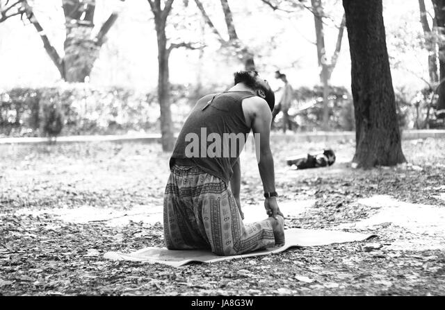 Young Indian man in camel pose (Ustrasana), in Cubbon Park, Bangalore. - Stock Image