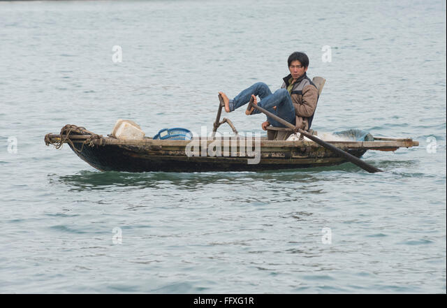 A small rowing boat used for fishing and transport, man traditionally using his feet to row, Halong Bay, Vietnam - Stock Image