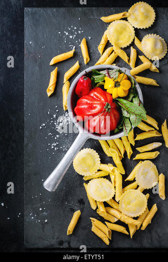 Homemade ravioli and garganelli pasta with flour and vintage colander with tomato RAF, salad leaves and yellow chili - Stock Image