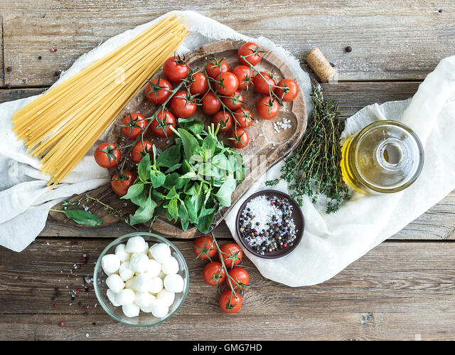 Ingredients for cooking pasta. Spaghetti, basil, cherry-tomatoes, mozarella, olive oil - Stock Image