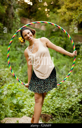 Mixed race woman playing with plastic hoop - Stock-Bilder