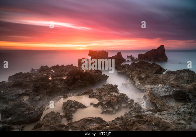 Calm ocean pink sky sunset - Stock Image