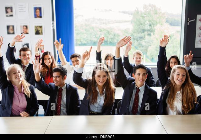 Teenage schoolchildren with hands raised in classroom - Stock Image