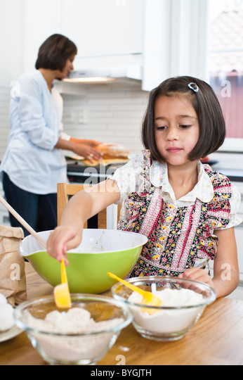 Girl baking in kitchen with mother in background - Stock-Bilder