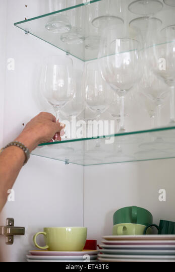 Close-up of a woman taking wineglass from cupboard, Munich, Bavaria, Germany - Stock-Bilder