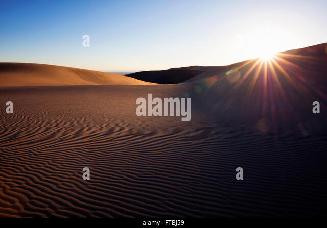 Sunlight peaking over sand dune in remote desert.  Great Sand Dunes National Park, Colorado, USA. - Stock Image