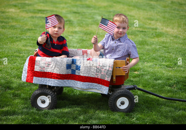 Two young boys sitting in wagon with American Flags - Stock Image