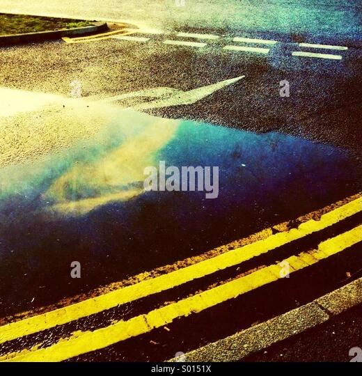Double yellow lines and reflection of cloud in puddle - Stock-Bilder