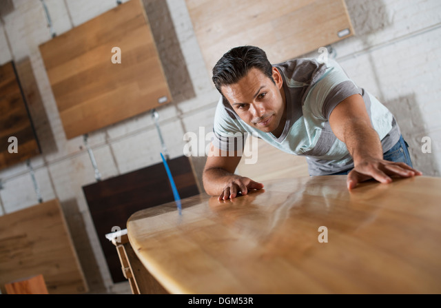 A young man in a workshop with stock of recycled and reclaimed timber. - Stock Image