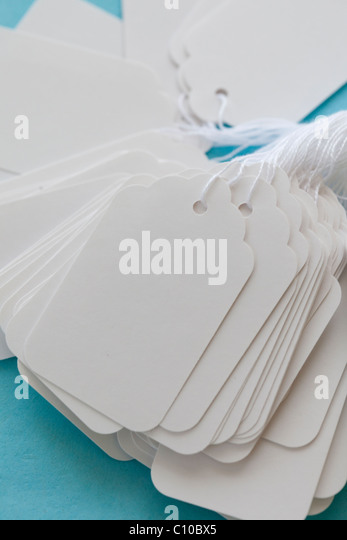 white blank price tag with string on blue cost - Stock Image