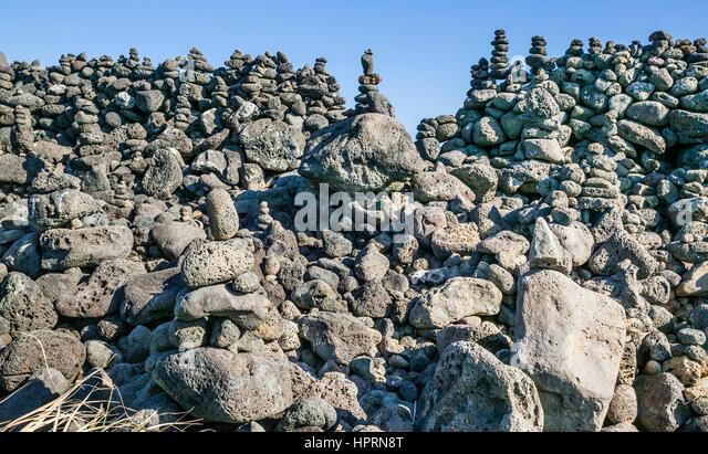 Republic of Korea, Jeju Island, East Coast, Onpyeong-ri, elaborate rock pile cairns at the coastal foreshore - Stock Image