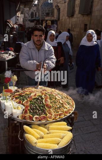 Israel Jerusalem Arab Quarters near Damascus Gate food vendor bazaar clothing - Stock Image