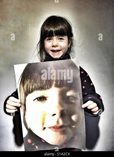 5-year old girl holding large photographic print of herself - Stock-Bilder