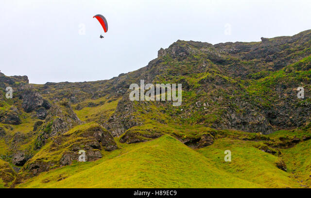 A hang glider flying at Reynisfjara, Iceland. - Stock Image
