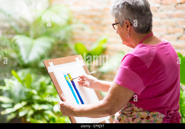 Senior woman painting an abstract picture in her garden - Stock-Bilder