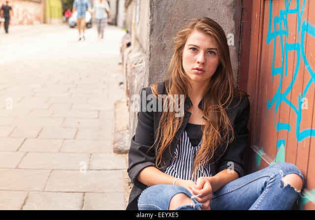 Young hipster girl sitting on the street. - Stock Image