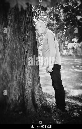 Portrait of old man leaning against a tree. Concept of old age and nature. Retirement and frustration. - Stock-Bilder