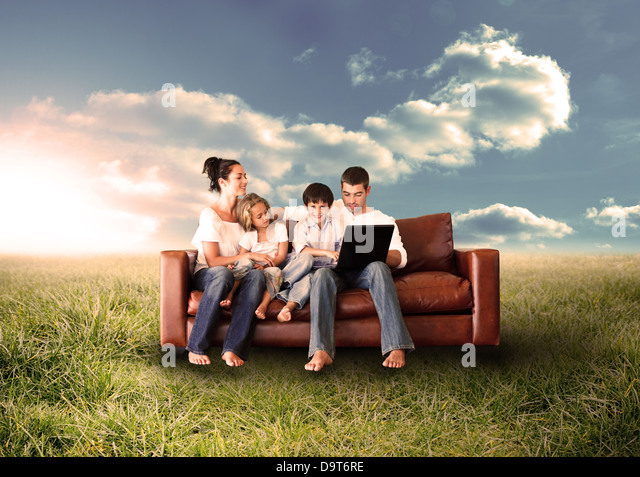 Happy family using the laptop in a field - Stock-Bilder