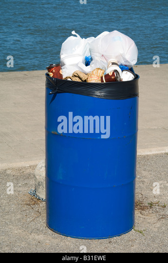A garbage can overflows with trash. - Stock Image
