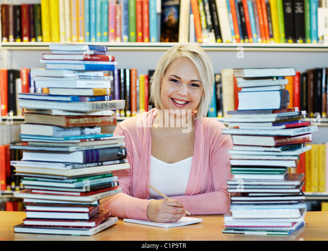 Young woman surrounded by books in library - Stock Image