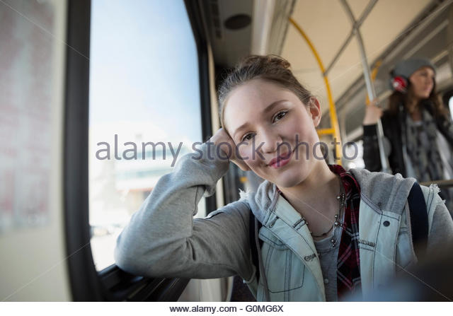 Portrait smiling teenage girl riding bus - Stock Image