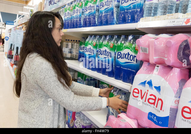 A young woman buying bottled water from the supermarket shelf, Tesco store interior, Suffolk UK - Stock Image