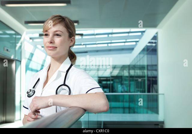 Portrait of nurse leaning on railing - Stock Image