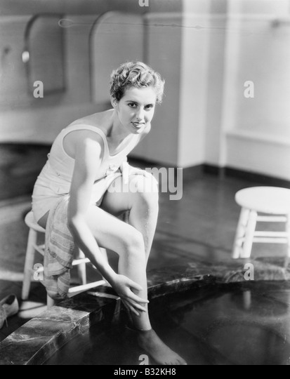 Portrait of woman soaking feet in footbath - Stock Image