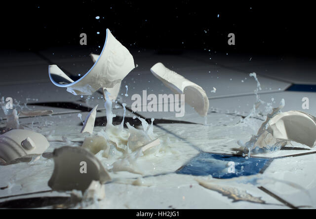 Cup of milk smashing on a kitchen floor - Stock Image