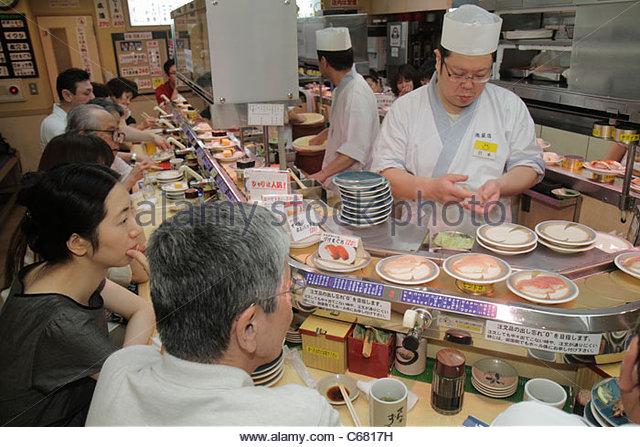 Tokyo Japan Ikebukuro kanji hiragana katakana characters Asian man woman sushi bar restaurant interior chef moving - Stock Image