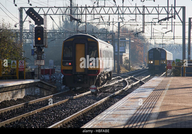 local trains passing on train line junction in a rail station in the uk - Stock Image
