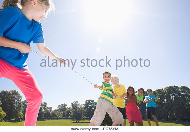 Group of children playing tug of war in park - Stock Image