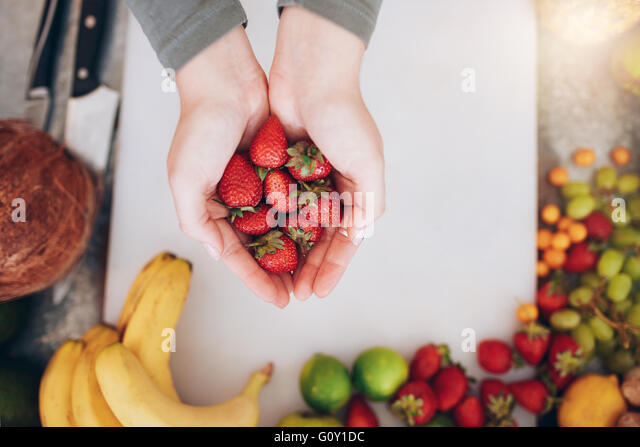 Top view close up shot of a woman's hands holding fresh strawberries over shopping board with fruits. Female - Stock Image