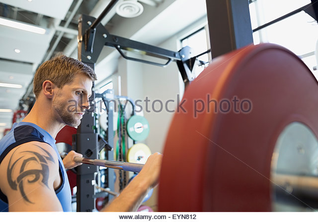 Man preparing for weightlifting at barbell in gym - Stock Image