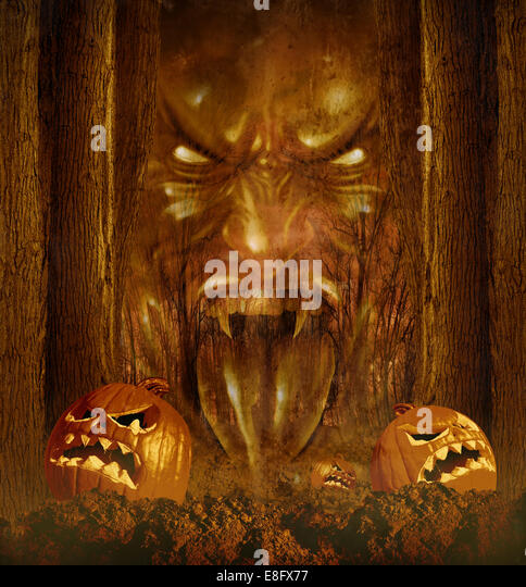 Halloween ghost concept as a creepy scary phantom appearing through a dark haunted forest with jack o lantern pumpkins - Stock Image