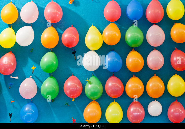 Germany, Bavaria, Munich, Multi coloured balloons and dart at oktoberfest - Stock Image