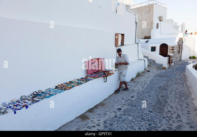 A street trader sells costume jewellery in Oia, Santorini in the Greek Islands. His market stall sits on a convenient - Stock Image