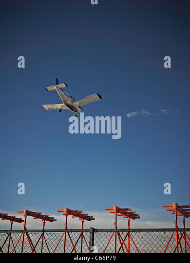 Airplane flying over fence - Stock Image