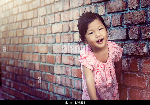 Portrait of girl leaning against wall - Stock Image
