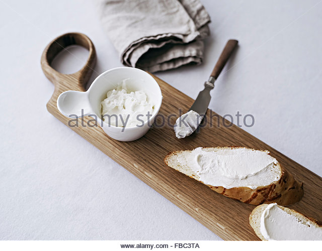 Bread on cutting board served with cream cheese - Stock Image