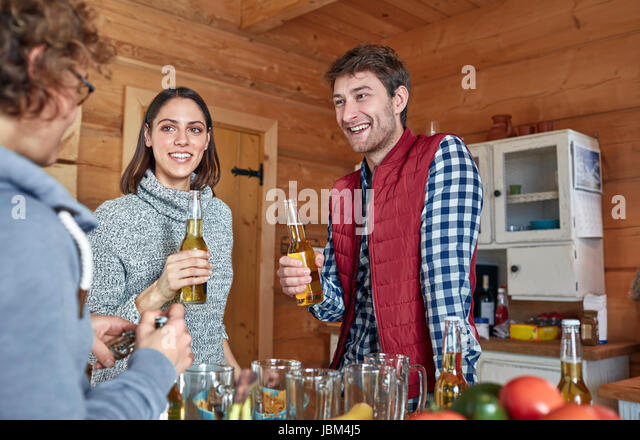 Friends drinking beer and hanging out in cabin kitchen - Stock-Bilder