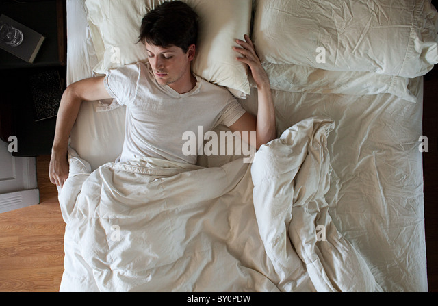 Man sleeping alone in double bed - Stock Image