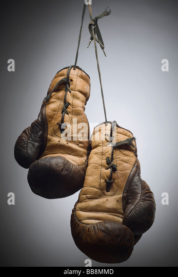 a pair of worn boxing gloves hanging on the string - Stock Image